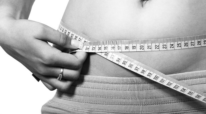 Image of person measuring their waist. If you are looking for a paleo weight loss plan or paleo diet weight loss advice, this article will get you on your way
