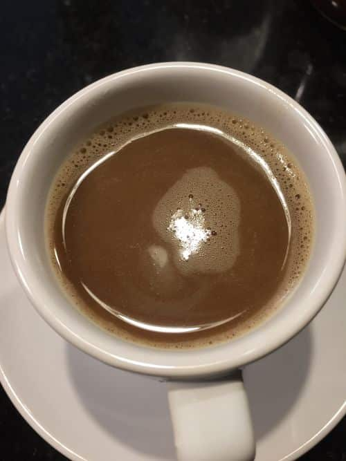 A photo from top of dark brew of coffee blocks in a mug. Coffee blocks are a way to start drinking butter in the morning with packets containing a bullet coffee coconut oil blend. If you are looking for coffee with butter in it, especially if you are often on the road, Coffee Blocks are a great option.