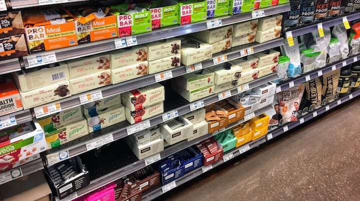 Photo of Paleo Approved Bars/Paleo Compliant Bars in grocery store - this article covers a number of prepackaged off the shelf brands. Would you love to find out where do you buy paleo bars from great brands like Steve's PaleoGoods? Read on for all of our research. We are fortunate that great companies like Freedom Bar exist these days. If you are searching for where to buy paleo bars you have come to the right place. There are a number of paleo clif bars like products with all Paleo and Whole30 allowed ingredients, listed in this article. Finding out info like where to buy paleo bars julian bakery bars is included in this article.